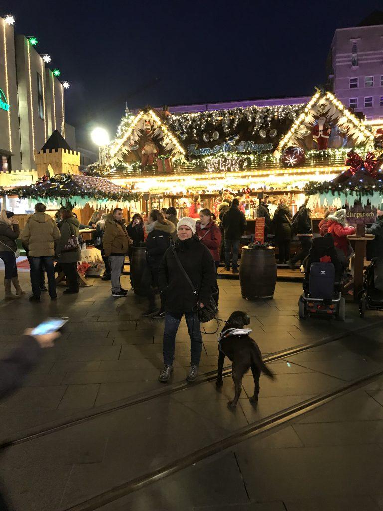 Bild vom Weihnachtsmarkt. Es ist bereits dunkel. Hinter mir der beleuchtete Glühweinstand. Ich schaue in die Kamera, Lieschen zieht es zum Glühweinstand
