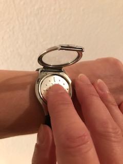 Foto: Taktile Armbanduhr mit geöffnetem Deckel. Mein rechter Zeigefinger ertastet die Uhrzeit.