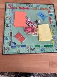 Monopoly-Spielbrett mit Aktionskarten und Geldscheinen mit Schwarz- und Brailleschrift beschriftet sowie zwei taktilen Würfeln
